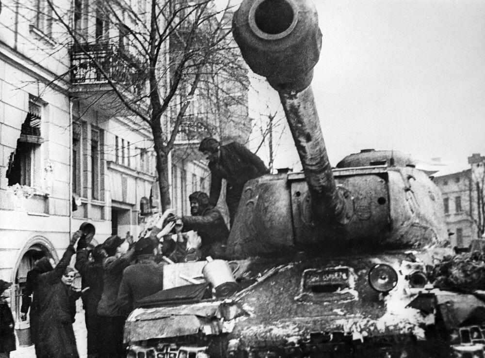 Polonya'nın Poznan kentinin sakinleri, ülkenin Nazilerden kurtarılması sırasında İS-2 tanklarla kentte ilerleyen Sovyet  askerlerini selamlıyor, 1945 II. Dünya Savaşı döneminde Sovyetler Birliği tarafından Eylül 1943 tarihinde ağır sınıf tank olarak geliştirilen Iosif Stalin tankı (veya IS olarak da bilinen Josef Stalin tankı), 122mm'lik bir top mermisi fırlatıyordu ve 46 ton ağırlığındaydı. Motoru 600 beygir güç üretiyordu. Bu tank genellikle öncü olarak kullanılıyor ve düşman cephesini yarıp geçme görevini üstleniyordu.