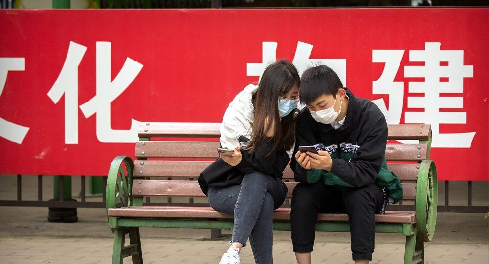 People wearing face masks to protect against the spread of the new coronavirus sit on a bench in front of a propaganda banner encouraging people to wear masks at a public park in Beijing