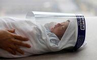 Koronavirüs döneminde doğan bebek aşı için geldiği hastanede yüz kaskı takılmış halde, Hanoi, Vietnam