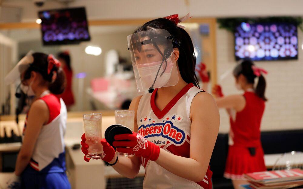 Japonya'nın başkenti Tokyo'daki 'Cheers One' restoranında ponpon kız kıyafetiyle müşterilere servis yapan maskeli ve eldivenli garsonlar