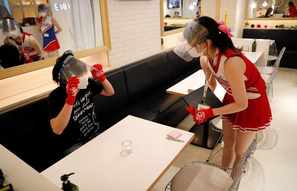 Spor kulübü temasıyla dekore edilmiş restoranda, garson kızlar ponpon kız takımı kostümleri giyerek müşterilerden sipariş alıyor