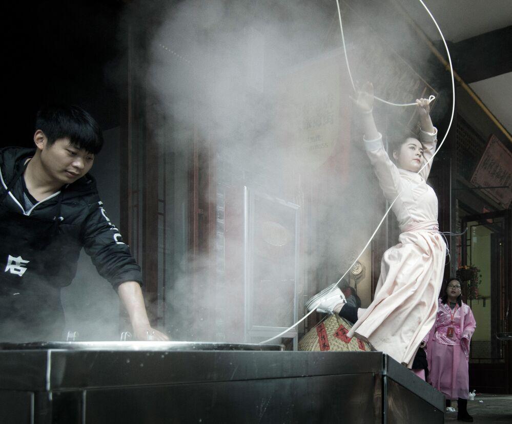 Yarışmanın Sokak Yemeği kategorisinin birincisi Çin'li Xueping Du'un fotoğrafında makarnadan geleneksel yemeğin pişirilme süreci görüntülendi
