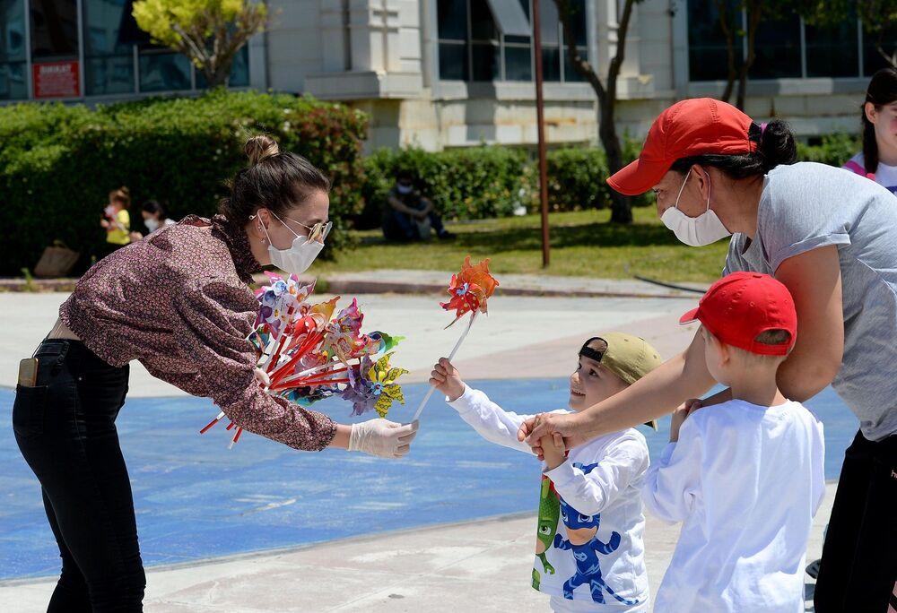Muratpaşa Belediyesi, 4 saatliğine sokağa çıkma izni verilen çocukları, Muratpaşa Atatürk Kent Meydanı'nda rüzgar gülleriyle karşıladı.