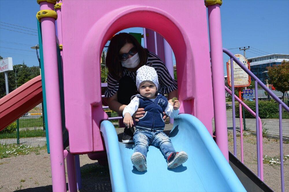 Ebeveynleri eşliğinde park ve bahçelere akın eden çocuklar, güneşli havanın ve parkların tadını çıkardı.