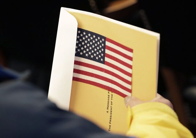 Ching Po Wong, from China, holds his information packet and an American flag during a naturalization ceremony, Friday, Jan. 17, 2020, in Cleveland. (AP Photo/Tony Dejak)