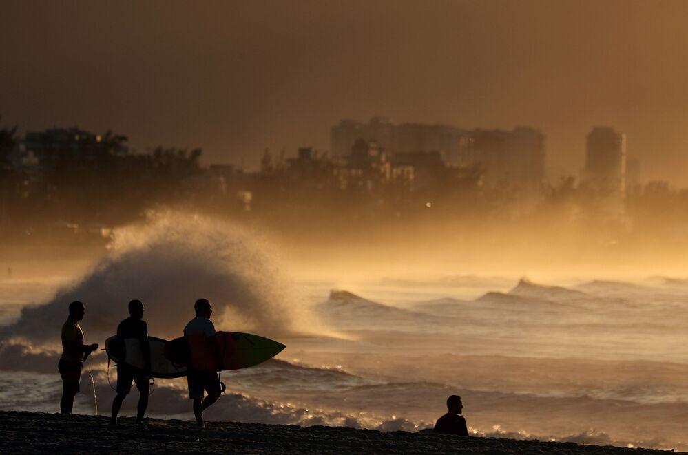 Brezilya'nın Rio de Janeiro kentindeki sahilde gün doğumunu izleyen sörfçüler