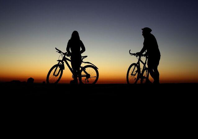 Almanya'nın Münih kentinde gün doğumunu izleyen iki bisikletçi