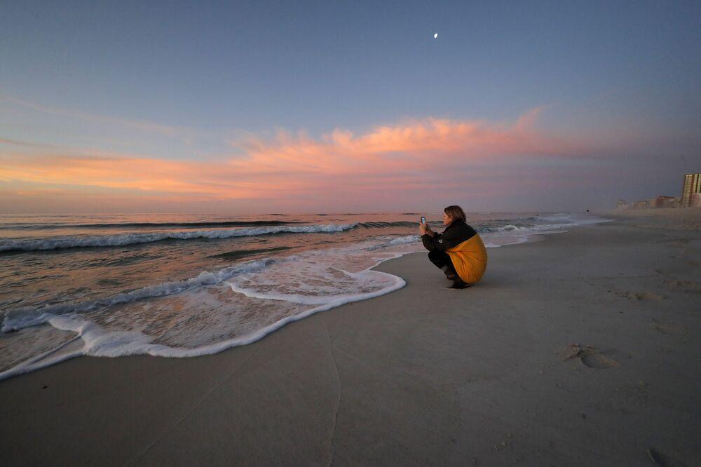 ABD'nin  Orange Beach sahilinde gün doğumunu görüntüleyen kadın