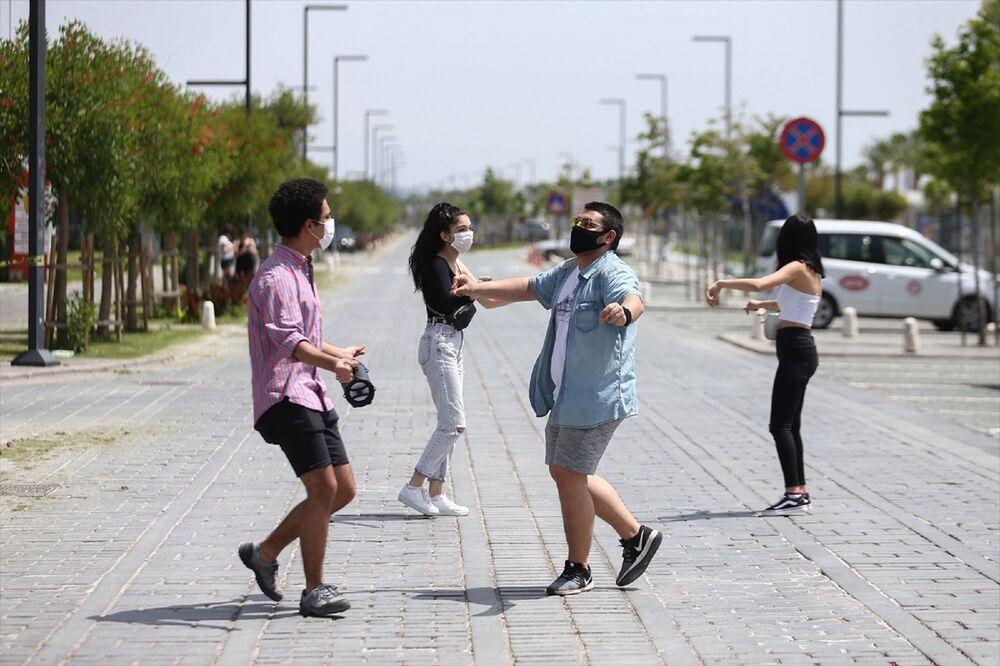 Antalya'da, yeni tip koronavirüs (Kovid-19) tedbirleri kapsamında getirilen sokağa çıkma kısıtlaması 4 saatliğine kaldırılan 15-20 yaş grubundaki gençler, uzun aradan sonra dışarıda olmanın keyfini yaşadı. Bir grup genç, dünyaca ünlü Konyaaltı Sahili'nin Kovid-19 tedbirleri kapsamında trafiğe kapatılan çift şeritli yolunda Erik Dalı şarkısı eşliğinde oynadı.