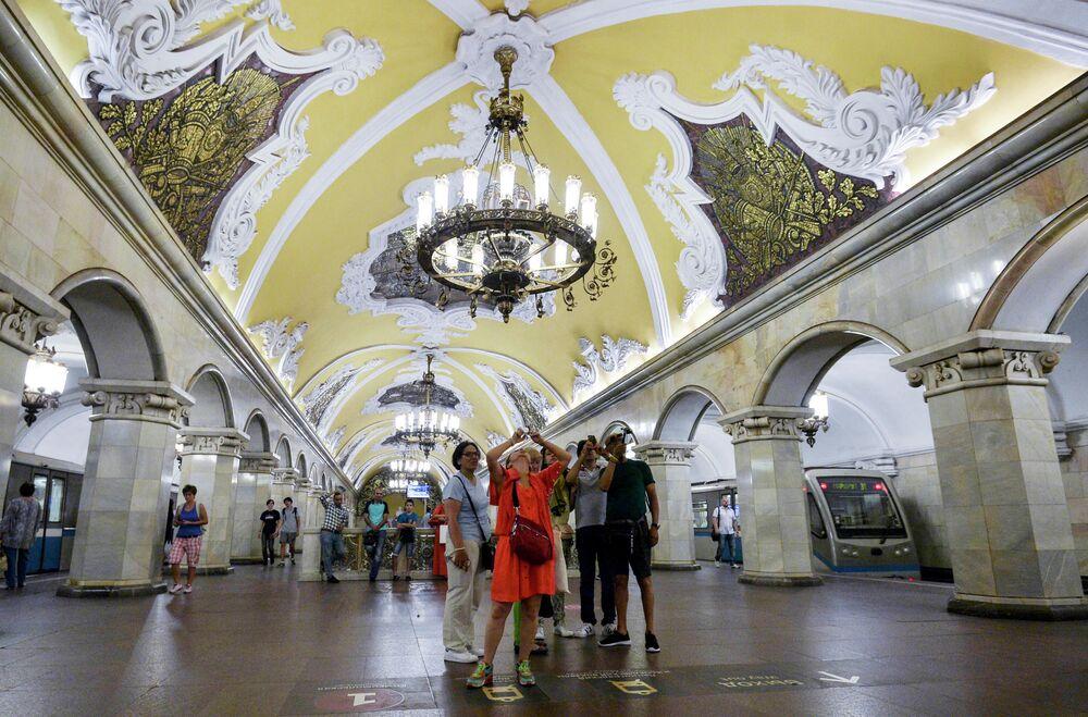 Turistler, Komsomolskaya İstasyonu tavanının fotoğrafını çekiyorlar.  Sarı tavan üstüne büyük avizeler ve mozaiklerle bu istasyon bir saraya benziyor