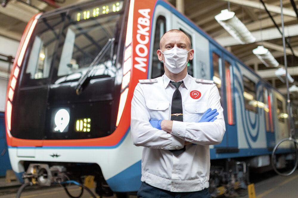 Koronavirüs salgınına karşı uygulanan önlemler kapsamında koruyucu maske ve eldiven takan Moskova metrosu makinisti