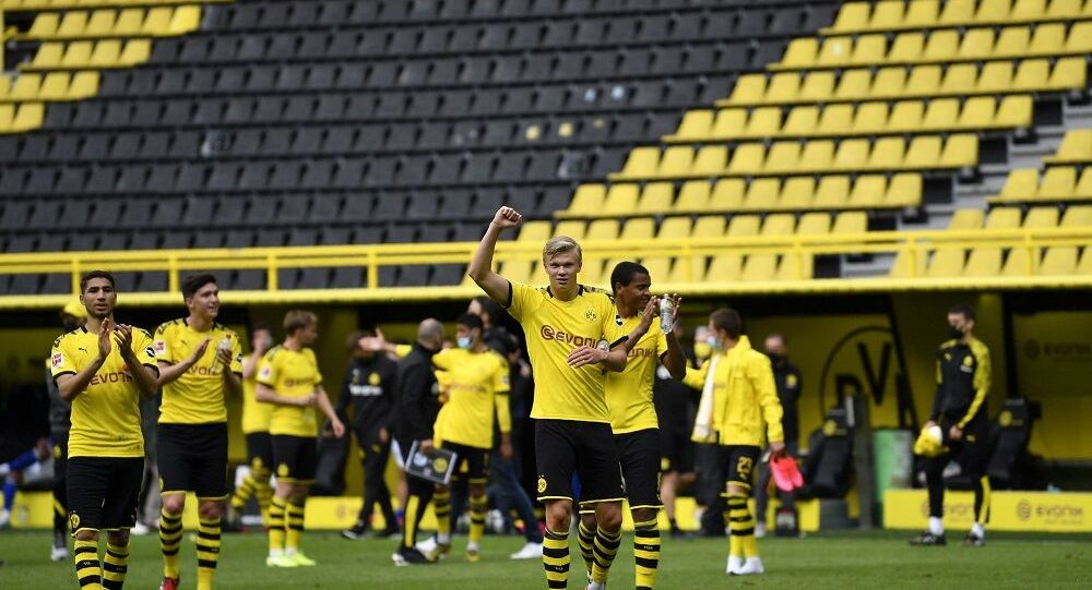 Dortmund's Erling Haaland, center, and his teammates celebrate at the end of the German Bundesliga soccer match between Borussia Dortmund and Schalke 04 in Dortmund, Germany, Saturday, May 16, 2020.