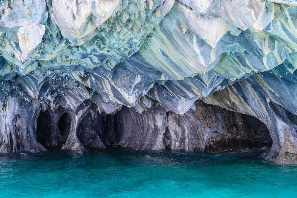 """Arjantin ve Şili arasında bulunan General Carrera Gölü'nün ortasında konumlanmış Mavi Mermer Mağaraları, Patagonya'daki en etkileyici turistik merkezlerden biri.  """"Mermer Şapel"""" ve """"Mermer Katedral"""" diye de anılan bu mağaralar, dev bir kireçtaşı yarımadasının dalgalar tarafından 6.000 yılda oyulmasıyla meydana getirilmiş ve bu sayede labirent şeklinde desenli ve renkli mağaralar ortaya çıkmış. Çok sayıda turist, bu ilginç oluşumu  görmek için bölgeyi ziyaret ediyor."""