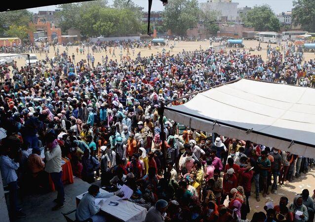 Hindistan'da  salgını dolayısıyla mahsur kalan ve tahliye olabilmek için kayıt yaptırması gereken binlerce göçmen işçi uzun kuyruklarda bekledi