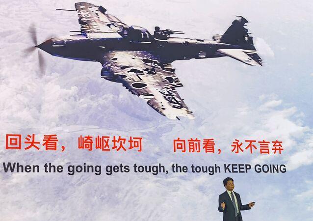 Huawei Global Analist Zirvesi 2020'de savaş uçağı görüntüsü ve İngilizce 'işler zorlaştığında güçlü olan sıyrılır geçer' yazısı altında açıklama yapan Huawei CEO'su Guo Ping, 18 Mayıs 2020, Şenzen, Çin