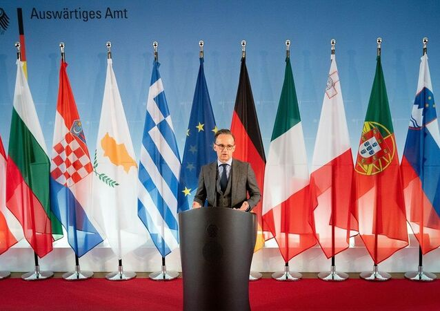 German Foreign Minister Heiko Maas stands in front of flags from different European countries as he addresses journalists on May 18, 2020