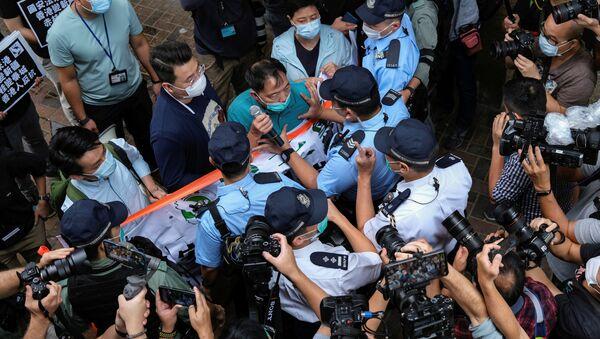 Hong Kong'da Çin İrtibat Ofisi önünde protesto düzenleyenler arasında bulunan demokrasi yanlısı vekil Wu Chi-wai, polisle arbede halindeyken - Sputnik Türkiye
