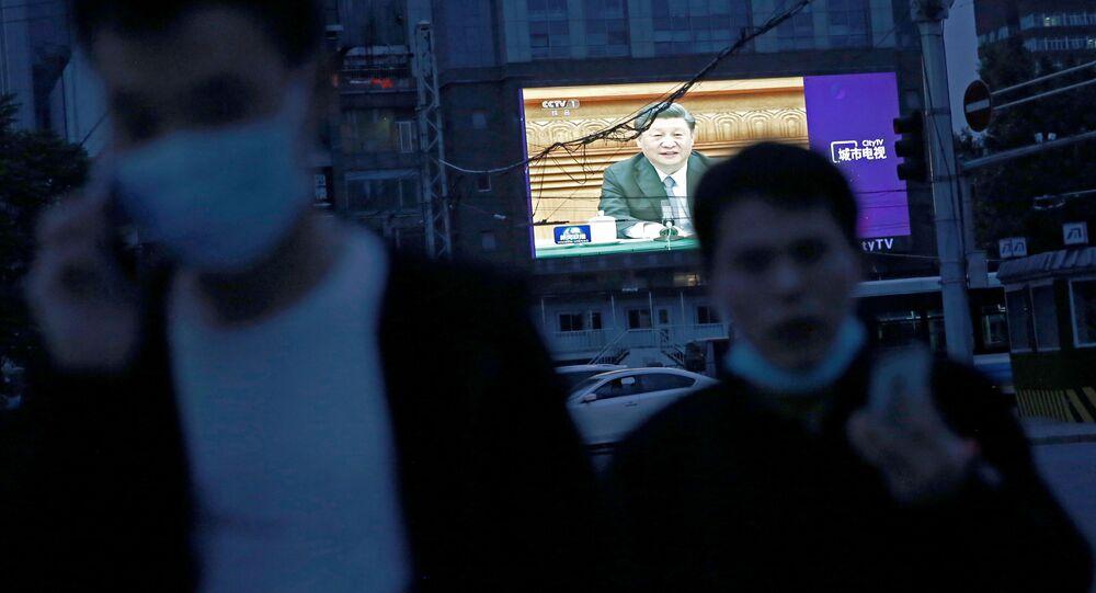 Çin Devlet Başkanı Şi Cinping'in Ulusal Halk Kongresi'nin açılışındaki görüntülerini aktaran dev ekran önünde yürüyen maske takmış Pekinliler