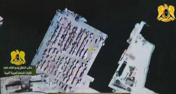İzmir deniz limanı ve trole yüklenen ve Libya'ya ulaştırılan zırhlı araçlar.Basın toplantısının ekran görüntüleri.