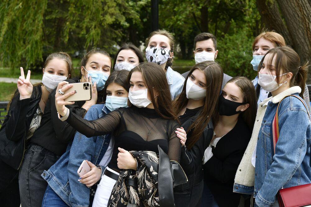 Rusya'nın Simferopol  kentinde maske takan ortaokul mezunları selfie çekiyor