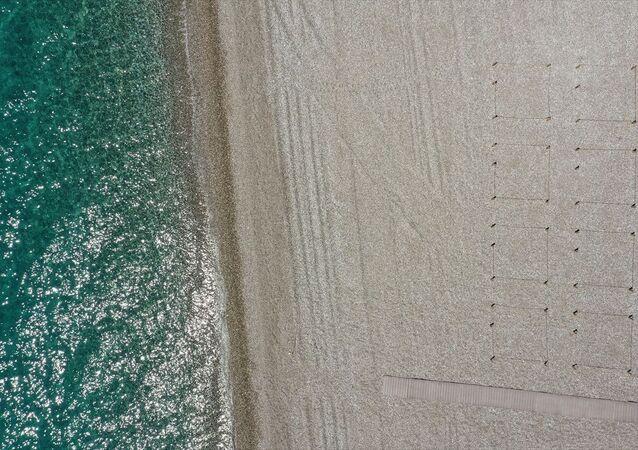 Antalya'nın dünyaca ünlü Konyaaltı sahili, denize girip plajda güneşlenecek yerli ve yabancı turistler için yeni tip koronavirüs (Kovid-19) tedbirlerine uygun olarak düzenleniyor.