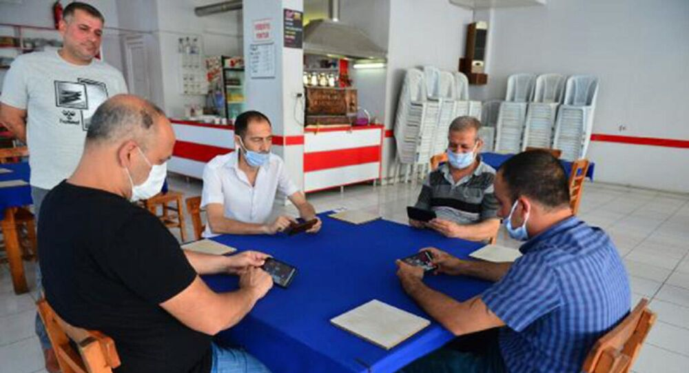Adana'da okey, tavla, iskambil oynanmaması kaydıyla açılan kahvehaneye gelen vatandaşlar, cep telefonlarındaki uygulamayla mobil okey oynadı.