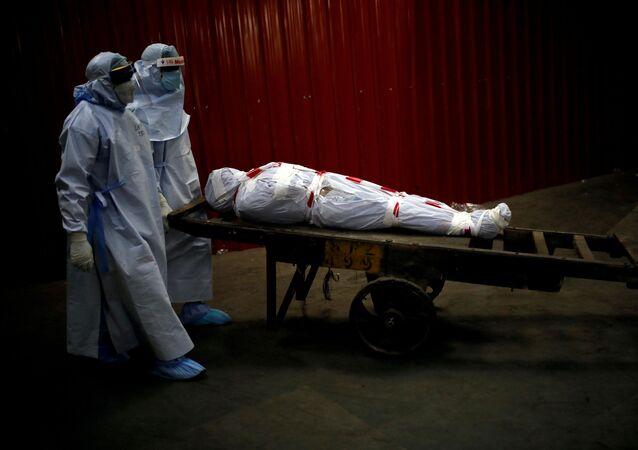 Hindistan'da koronavirüs sebebiyle yaşamını yitiren bir hastayı nakleden sağlık görevlileri
