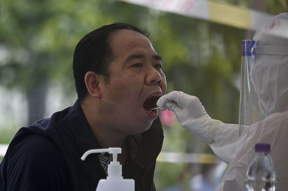 Kovid-19 vakaların artmasının ardından 350 bin vatandaşına koronavirüs testi yapılan Pekin'de maskeli insanların kalabalık bir şekilde test için sırada beklemeleri başkentin yaygın manzaralarından biri olmaya başladı.