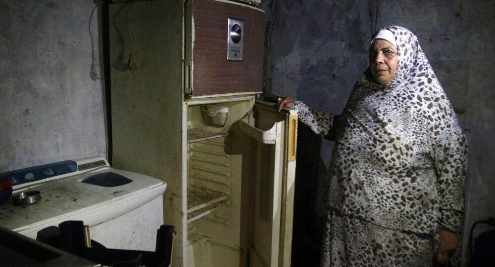 Lübnan'da AFP'nin ziyaret ettiği Sayda kenti sakini bir kadın, buzdolabını açarak içinin bomboş olduğunu gösterdi.