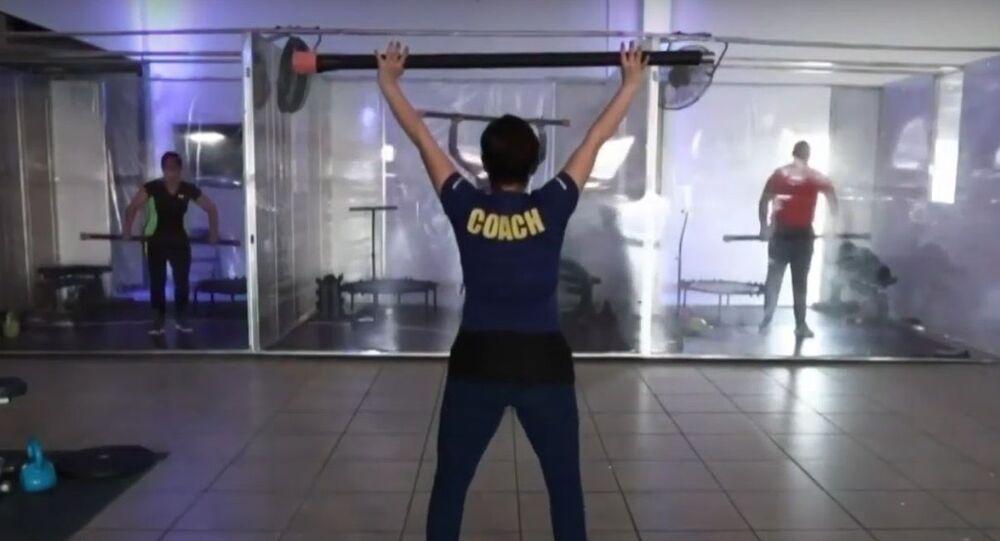 Meksika'da bir salonda şeffaf bölmeler içinde spor yapılıyor