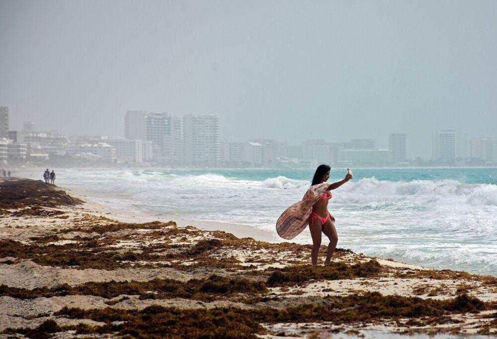 Dev toz  ve kum bulutunun ulaştığı Meksika'nın Cancun kentinin sahilinde selfie çeken kadın
