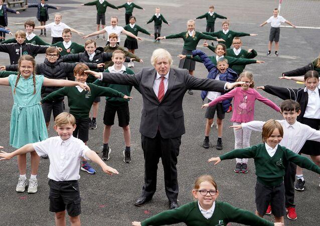 Başbakan Boris Johnson okul çocuklarıyla birlikte koronavirüse karşı sosyal mesafe egzersizi yaparken, Hemel Hempstead, 19 Haziran 2020