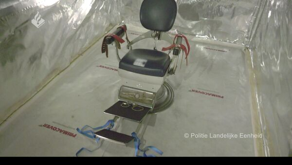 Wouwse'deki depoya Hollanda polisinin düzenlediği operasyonda bulunan konteyner içindeki işkence odasının dişçi koltuğu düzeneği - Sputnik Türkiye